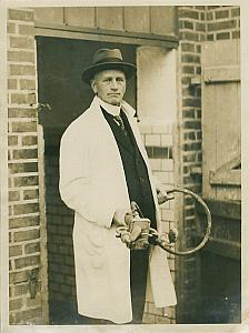 Man in White Coat Holding Tool device old Photo 1920's